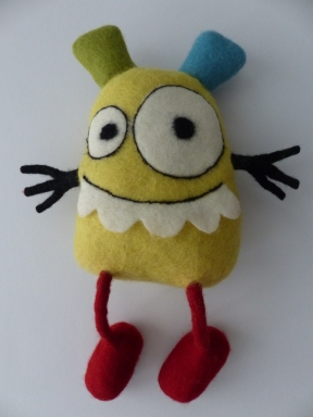 Nach dem letzten Feintuning mit der Filznadel und schwarzem Wollfaden aus Seide und Mohair ist das gelbe Monster fertig.