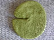 Die Schablone wird mit grüner Merinowolle im Vlies umhüllt.