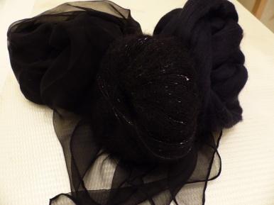 Zutaten für den Ausgehschal: schwarzer Chiffon, feine schwarze Merinowolle, schwarze Seiden-Mohairmischung mit Lurexfaden