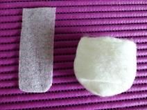 Die Schablone wird entfernt und die Filzhülle vorsichtig mit den Fingern geweitet. Es dürfen kleinere Löcher entstehen. Die Filzhülle in der Hand kurz kneten und über das Glas ziehen. Solange dehnen und überziehen bis es passt.